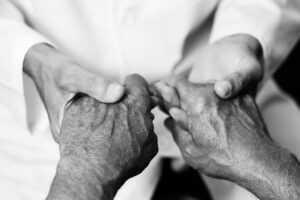 closeup of a caucasian man, in a white coat, holding the hands of a senior caucasian man, in black and white